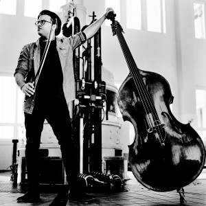 Adam Ben Ezra standing inside the hydroelectric power plant holding his double bass and fiddlestick.