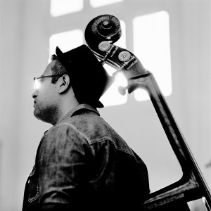Adam Ben Ezra's head with his double bass in front of a window.