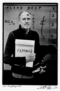 Anton Corbijn holding an envelope in his hand with names of his books.