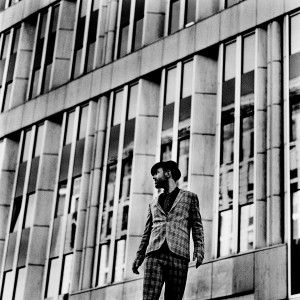 Charlie Winston standing in front of an office building looking back wearing hat and a suit.