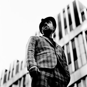 Charlie Winston standing in front of an office building wearing a hat and a suit.