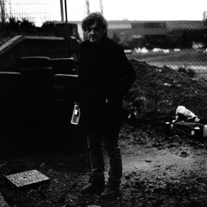 Emir Kusturica standing wearing black and holding a bottle of alcohol.