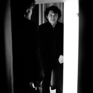 Emir Kusturica posing with his reflection in the mirror in changing room in the boutique.