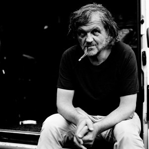 Emir Kusturica sitting and smoking a cigarette.