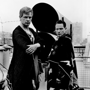 Gus Gus members Daniel Agust Haraldsson and Birgir Porarinsson posing at two tubes on a rooftop of a building with city view in the background.
