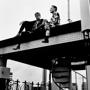 Gus Gus members Daniel Agust Haraldsson and Birgir Porarinsson sitting on a rooftop floor above the stairs wearing high heels.