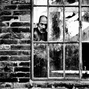 Jean-Marc Barr standing behind an old broken window in a brick house.