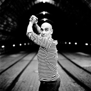 Jean-Marc Barr posing and making gesture in front of a tunnel wearing striped t-shirt.