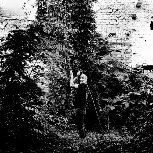 Jean-Marc Barr posing with a giant plants in a jungle house wearing black.
