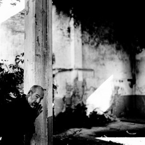 Jean-Marc Barr posing at a pillar in an old ruined house.
