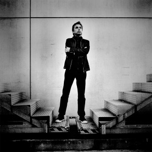 Jean-Michel Jarre standing between two stairways with his hands crossed on his chest.
