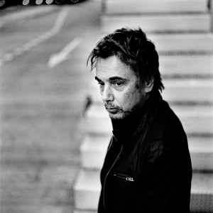 Jean-Michel Jarre standing at a stairway wearing black.