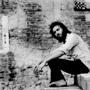 Jean Rondeau sitting on the stairs with old brick wall in the background.