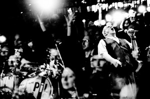 Double exposure of John Lydon Pil on the stage at his concert and faces in the audience.