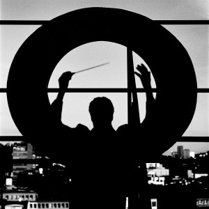 Kevin Griffiths in a conducting pose with his hands up holding baton on the rooftop of a building with giant letter O and the city view in the background.