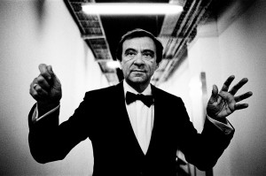Marcello Rota wearing a tuxedo making gesture conducting without a baton.