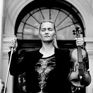 Mari Samuelsen with eyes closed in front of a door holding violin and a fiddlestick.