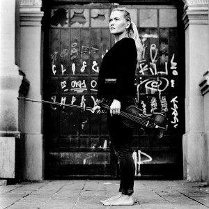Mari Samuelsen standing barefoot in front of door with graffiti holding violin and fiddlestick.