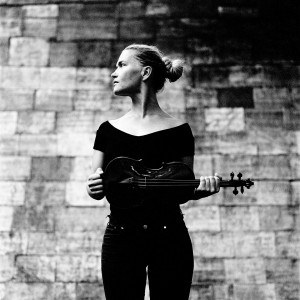 Mari Samuelsen holding violin looking to the left with brick wall in the background.