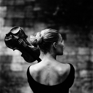 Mari Samuelsen from the back holding violin with brick wall in the background.