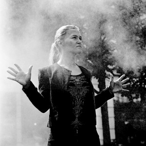 Mari Samuelsen making gesture with her palms in the steam with trees in the background.