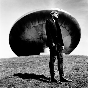 Cyborg artist Neil Harbisson standing in front of ufo spaceship monument.