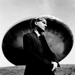 Neil Harbisson standing at a monument of ufo spaceship.