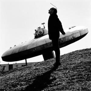 Cyborg artist Neil Harbisson standing at statue of ufo spaceship.