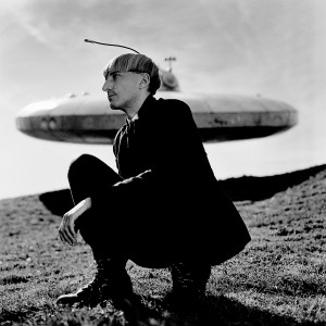 Cyborg artist Neil Harbisson squating in front of ufo spaceship monument.
