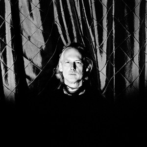 Richard Dorfmeister in front of a checked curtain.