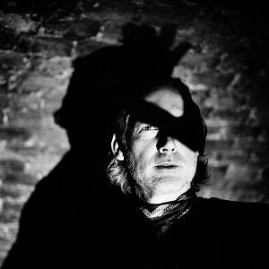 Face of Richard Dorfmeister with one eye covered with the shadow of his hand with the brick wall in the background.