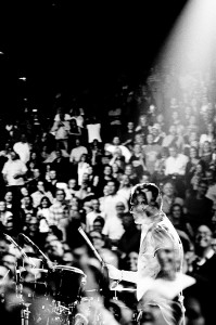 Double exposure of U2 drummer Larry Mullen Jr. playing drums with the people in the audience.